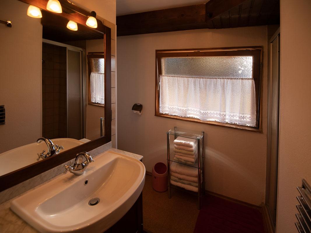 Blick ins Badezimmer mit Spiegel, Waschbecken, Dusche und Fenster_private-Ferienwohnungen-Preisch_Bad-Ischl-im-Salzkammergut