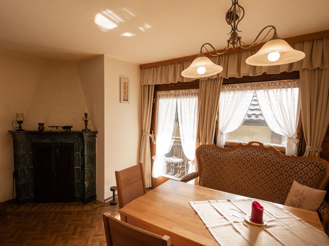 Küchentisch mit Kachelofen und Zugang zum Balkon im Hintergrund_private-Ferienwohnungen-Preisch_Bad-Ischl-im-Salzkammergut