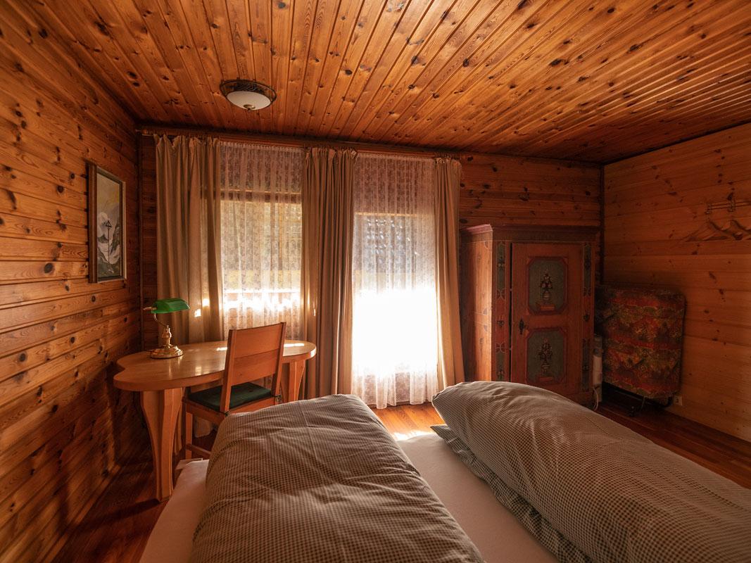 Schlafzimmer_Blick zur Balkontüre mit altem Bauernkasten_private-Ferienwohnungen-Preisch_Bad-Ischl-im-Salzkammergut