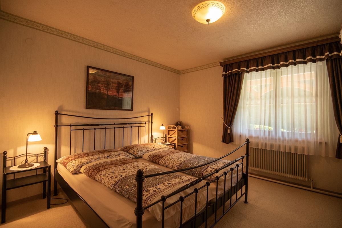 Schlafzimmer Ferienwohnung 1_Doppelbett mit Nachtkästchen und Fenster zur rechten Seite_private-Ferienwohnungen-Preisch_Bad-Ischl-im-Salzkammergut