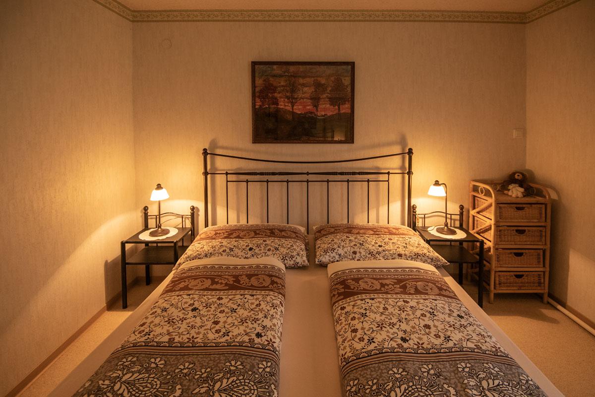 Schlafzimmer_Ferienwohnung 1_Blick aufs Doppelbett mit Nachtkästchen und Lampen_private-Ferienwohnungen-Preisch_Bad-Ischl-im-Salzkammergut