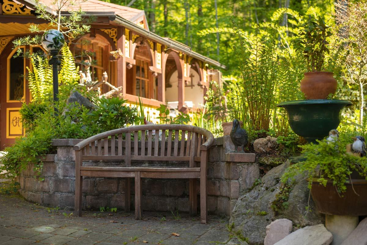 Holzbank im Innenhof vorm Teich mit Gartenfiguren und Pflanzen_private-Ferienwohnungen-Preisch_Bad-Ischl-im-Salzkammergut