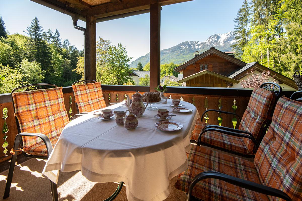 Ferienwohnung 1_Blick auf die Terrasse mit gedecktem Frühstückstisch und Bergblick_private-Ferienwohnungen-Preisch_Bad-Ischl-im-Salzkammergut
