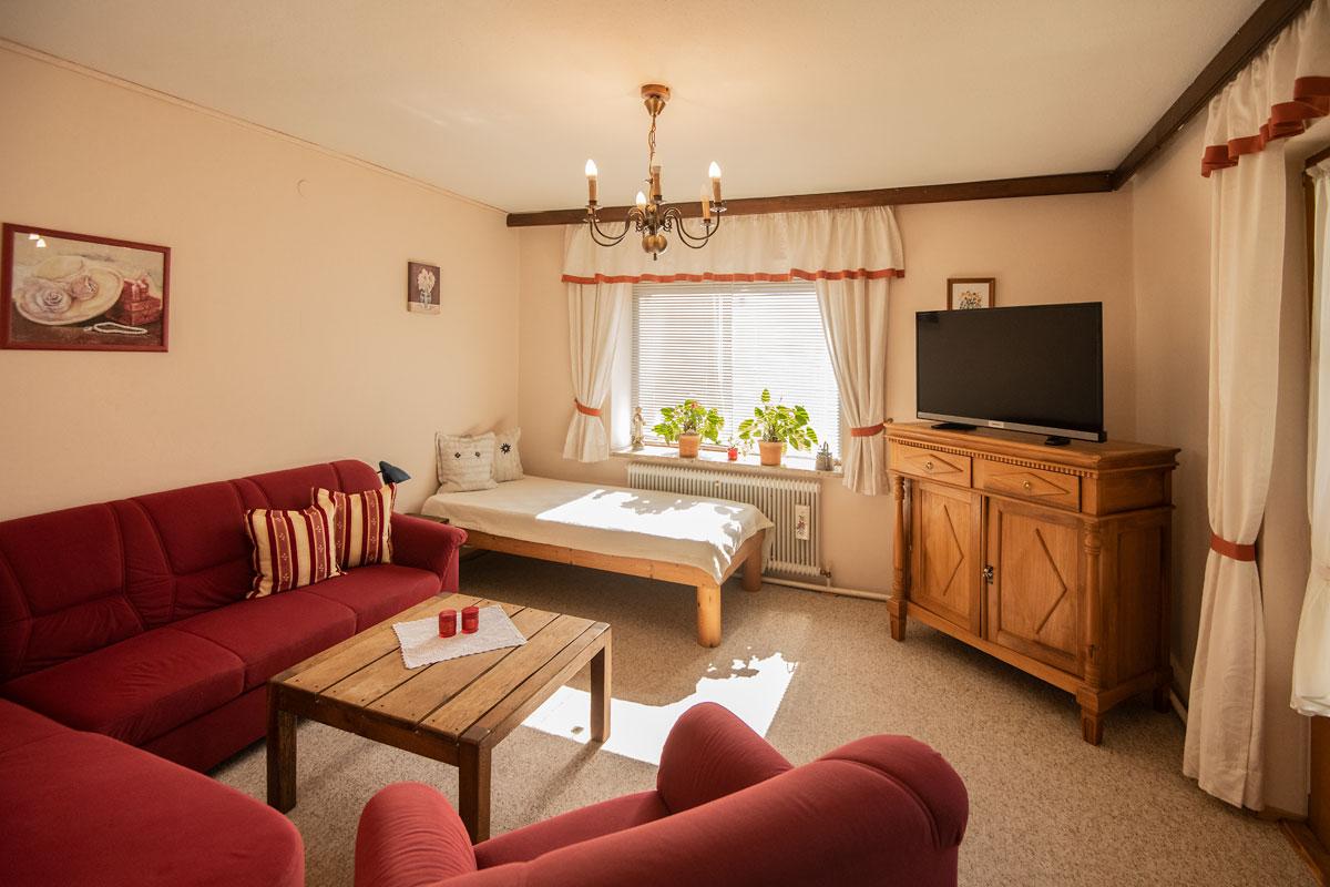 Wohnzimmer mit Fernseher und weinroter Couch zur linken Seite__private-Ferienwohnungen-Preisch_Bad-Ischl-im-Salzkammergut