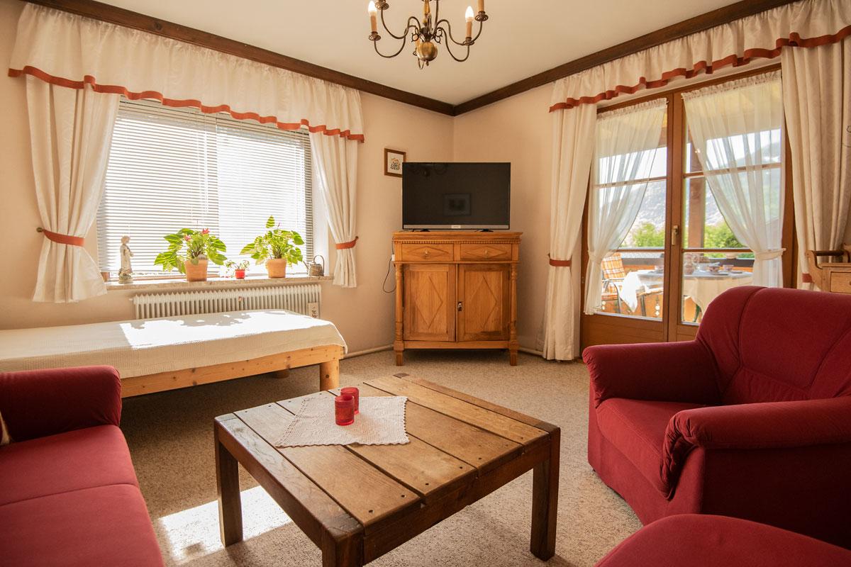 Wohnzimmer mit Blick von der weinroten Couch zum Fernseher_private-Ferienwohnungen-Preisch_Bad-Ischl-im-Salzkammergut