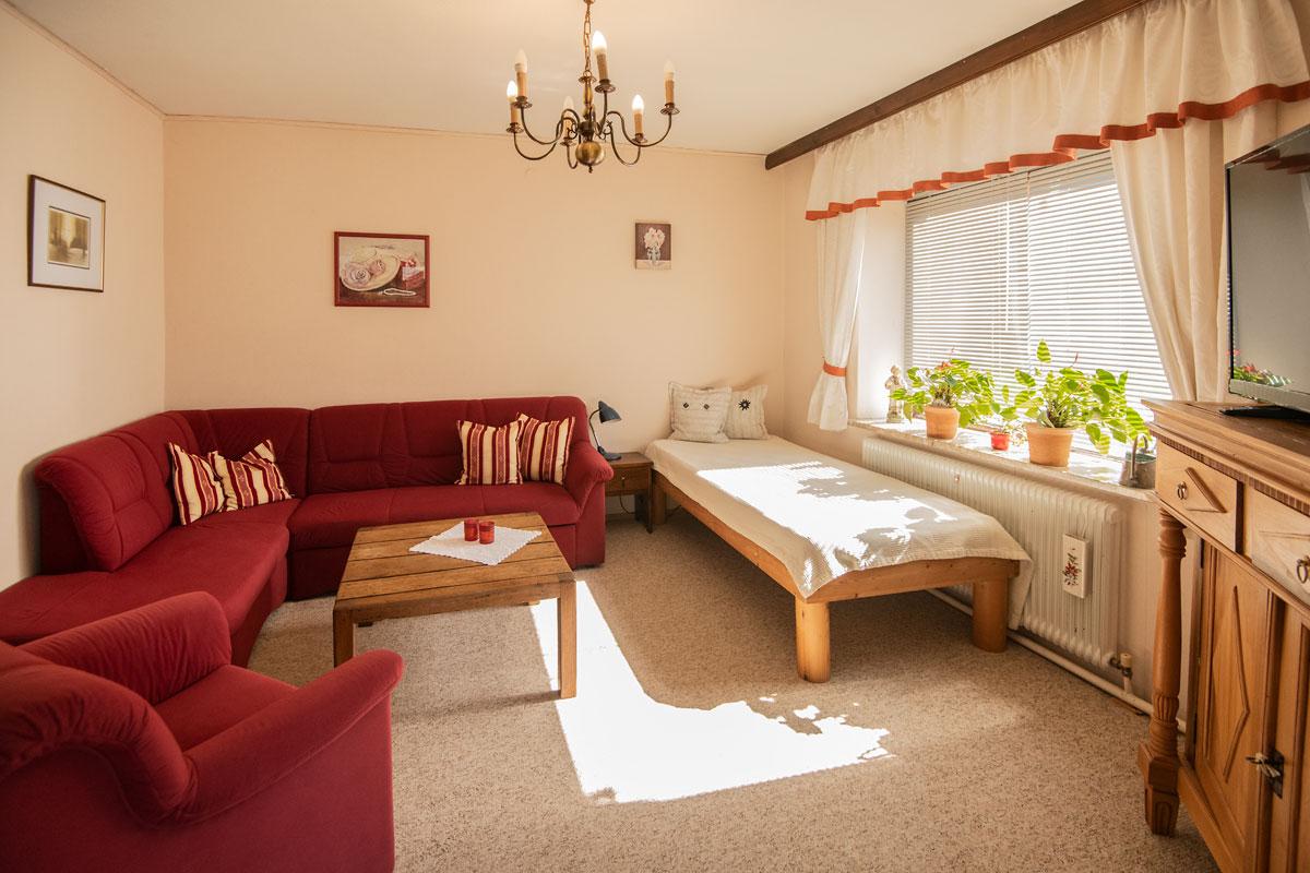 Blick auf die weinrote Couch im Wohnzimmer_private-Ferienwohnungen-Preisch_Bad-Ischl-im-Salzkammergut